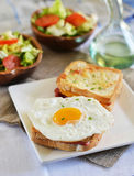 French sandwich croque-monsieur with green salad. On a white plate stock photo
