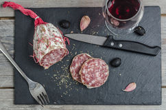 A french saucisson - dry summer sausage on the black background, with a knife, fork, garlic and olives and red wine. Royalty Free Stock Photo