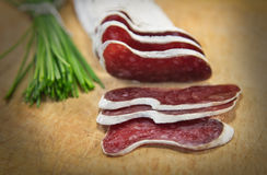 French sausage with herbs. French meat sliced with green herbs royalty free stock photo