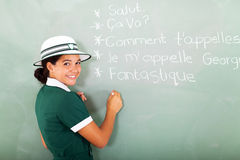 French schoolgirl. Portrait of cute French schoolgirl writing on chalkboard Stock Images