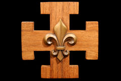 French Scout Emblem. Antique scouting fleur-de-lis on solid oak wood. Isolated on black royalty free stock photos