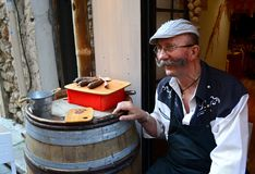 French seller invites tourists to taste sausages. The extraordinary seller invites tourists to taste sausages in Antibes, France Stock Photography