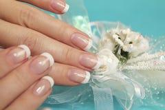 French short wedding manicure . French short wedding manicure on female hand close up with decoration on a blue background stock photo
