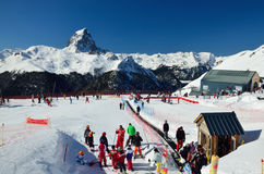 French ski resort against the peak du Midi d'Ossau. Gourette, France - March 09 2013: Skiers are at the ski resort Gourette against the famous mountain Pic du Stock Photos