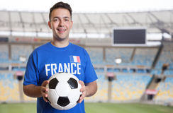 French soccer fan with ball at stadium. Laughing french sports fan with ball at soccer stadium Royalty Free Stock Image