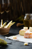 French soft cheese from Brittany region and sliced brie with pear, honey and glasses of white wine Stock Image