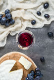 French soft cheese from Normandy region sliced on a wooden cut with red grapes and glass of red wine. On dark rustic table, blurred background, top view Stock Image