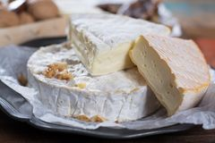 French soft cheeses - camembert, marcaire, munster, brie - delicious dessert with nuts and dried fruits royalty free stock image