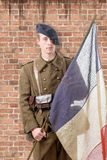 1940 french soldier with a flag, wall of red brick at the back Royalty Free Stock Images