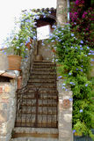 French Stairway with Blue Flowering Vines. Outside stone stairway with blue flowering vines in French medieval village of Mougins.  Rusty iron gates secure Stock Image