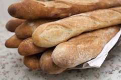 French sticks. Nine French loaves on a floral tablecloth in a bakery stock image