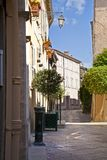 French street and alley. Typical french side road with cobblestones and homes and flower pots Stock Image