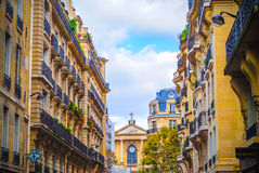 French street in Paris with a church. French street in Paris  with amazing plats during daytime Royalty Free Stock Photos