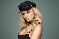 French style lady posing in black beret. French style female model posing in black beret. Blonde beautiful woman with glamour makeup and long curly hair Stock Images