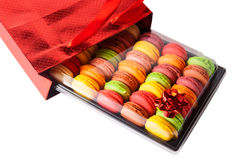 French sweets macaroons in a red gift bag with a bow. Selective focus Stock Photography
