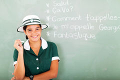 French teen girl. Portrait of smiling french teen girl holding chalk in front of chalkboard in classroom stock photo