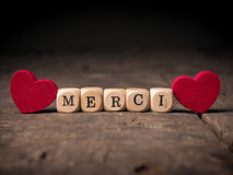 French thank you. Small wooden dices with the French word of Thank you with two red heart shapes on wood Stock Images