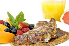 French Toast. Plate with slices of French Toast, decorated with fresh fruits and a glass of orange juice Royalty Free Stock Photos