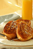 French Toast. Three pieces of french toast and syrup; spinkled with powdered sugar; orange juice and blue napkin on side of plate Stock Photo