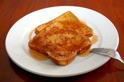 French toast. With syrup on a white plate with a fork royalty free stock photo