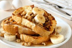 French toast with bananas, walnuts and maple syrup. Plate of delicious French toast with bananas, walnuts and dripping maple syrup Royalty Free Stock Image