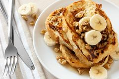 French toast with bananas, walnuts and maple syrup. Plate of delicious French toast with bananas, walnuts and dripping maple syrup, overhead view Royalty Free Stock Photo