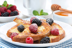 French toast with berries and powdered sugar. Horizontal royalty free stock photo