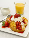 French toast and fresh strawberries. Topped with powdered sugar whipped cream served with a glass of orange juice stock images