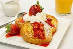 French toast and fresh strawberries. Topped with powdered sugar whipped cream served with a glass of orange juice royalty free stock photos