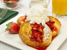 French toast and fresh strawberries. Topped with powdered sugar whipped cream served with a glass of orange juice royalty free stock photography