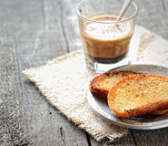 French toast on a plate and coffee with milk, napkin on a wooden background Royalty Free Stock Photos