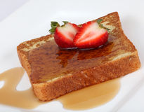 French toast with syrup and strawberry. On a white plate Royalty Free Stock Photography