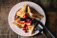 French toast served with syrup and fresh berries Royalty Free Stock Images