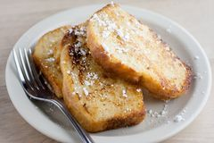 French Toast. On a white plate sitting on a wooden background Stock Photo
