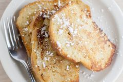 French Toast. On a white plate sitting on a wooden background Royalty Free Stock Photography