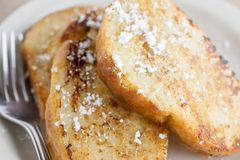 French Toast. On a white plate sitting on a wooden background Royalty Free Stock Photos