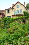 French town house with summer garden. A photograph showing an old stone house in a small mediaeval town in the south west of France, Europe, and the beautiful Stock Images