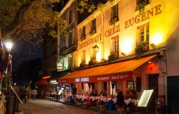 The French traditional cafe Chez Eugene at night, Paris, France. Paris, France-02 may 2018 : The French traditional cafe Chez Eugene located in Montmartre area stock photography