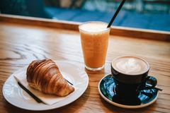 French traditional croissant dessert next to coffee cappuccino and orange juice in a cafe for breakfast. Stock Photography