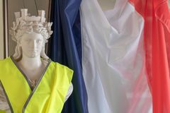 The French tricolor and Marianne, the symbols of the Republic and the yellow jackets protester Gilet jaune. Images dedicated to the movement of Yellow Vests and stock photo