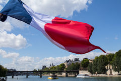 French Tricolour flag and Paris Seine. A French Tricolour flag blows in the wind against a cloudy blue sky over the Seine in Paris. The view is taken at river Stock Photography