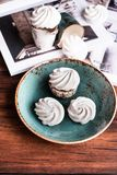 French vanilla meringue cookies or dessert made from whipped egg whites and sugar on a plate on a wooden table, selective focus. S. Weet food. Image with copy royalty free stock photography