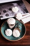 French vanilla meringue cookies or dessert made from whipped egg whites and sugar on a plate on a wooden table, selective focus. S. Weet food. Image with copy stock photos
