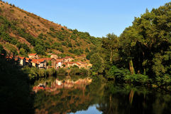 French village at sunset. The picturesque French village of Bouillac mirrored by the Lot river at sunset. Aveyron, France Royalty Free Stock Photo