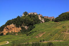 French vineyard in the jura region. Small french village on a hill top with green vineyard on the hill side in the jura region in france royalty free stock photo