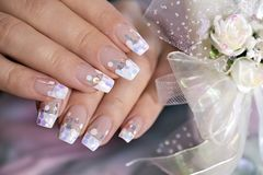 French wedding manicure with translucent glitters, white dots. Close-up. Nail art royalty free stock photography