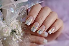 French wedding manicure with translucent glitters, white dots. Close-up. Nail art stock photos