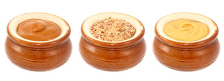 French, wholegrain and Dijon mustards served in ceramic pots Royalty Free Stock Photos