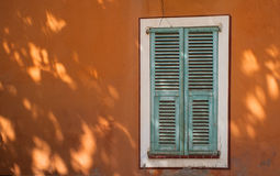 French window shutters background. Green french window shutters on orange wall tree shadows Royalty Free Stock Photography