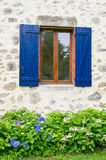 French window with shutters. French window with blue shutters and flower garden outdoor Royalty Free Stock Image